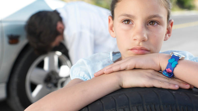 Girl waiting for father to fix tire